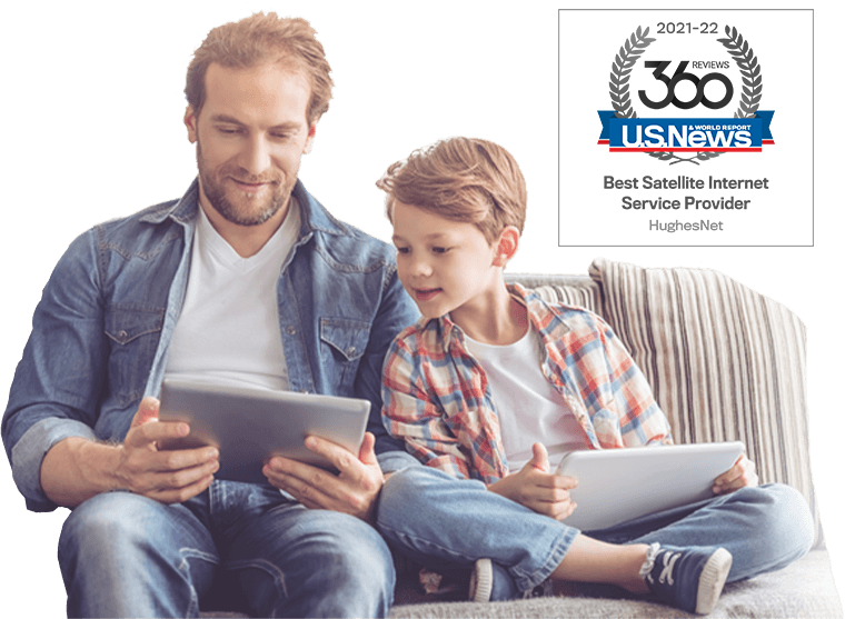 Father and son on a sofa reading on tablets using satellite internet service.